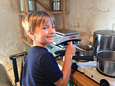child smiling stirring soap mixture at a Jean Barry workshop